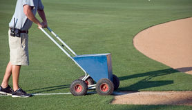 White Chalk Line. A young man prepares a baseball field for the game Stock Photo