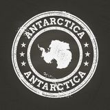 White chalk texture grunge stamp with Antarctica. White chalk texture grunge stamp with Antarctica map on a school blackboard. Grunge rubber seal with country stock illustration