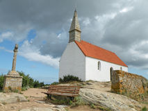 White Chapel. Sunlit white chapel pictured against dark cloudy sky Stock Images