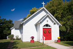 White chapel. Bright white chapel with red doors decorated with fall flowers royalty free stock photos