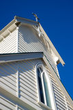 White chapel. Front of a small wooden white chapel against a blue sky. With a cross on the top Stock Photo