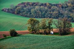 White chapel nestled in the trees in the last rays of the sun, on the background of green hills and autumn shrub.Chapel st.Barbara Stock Photos