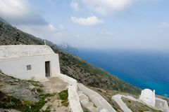 White chapels on a cliff in Olympos, Karpathos island Greece. Two family chapel hanging on the wall of a cliff on the west side of the village of Olympos village Royalty Free Stock Photos