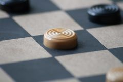 Checker on a checker board. A white check waits to be moved on a black and white wooden checkered board stock photos