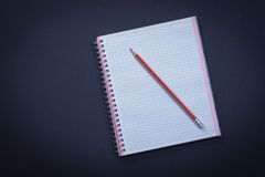 White checked copybook with red pencil on black Royalty Free Stock Photos