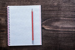 White checked copybook with red pencil on pine Stock Photos
