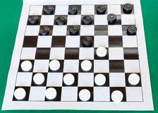 White checkered sheet board with draughts. On green baize table royalty free stock image