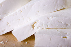 White cheese. White goat cheese block on wooden board Royalty Free Stock Photo