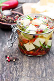 White  cheese cubes and herbs dipped in olive oil in small jar o Stock Image