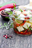 White  cheese cubes and herbs dipped in olive oil in small jar o Royalty Free Stock Photo