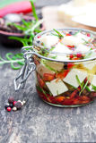 White  cheese cubes and herbs dipped in olive oil in small jar o Stock Images