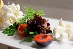 White cheese with fresh herbs, mint, plum and cherry tomatoes. White cheese with some fresh herbs, mint, plum and cherry tomatoes Royalty Free Stock Photos