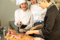 White chef teaches trainee to cut a chicken. Master Class on the background of the kitchen. White chef teaches trainee a group of people to cut a chicken. Master royalty free stock photo