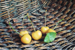 White cherry. Some white cherry in the wicker basket. Wicker basket texture at the background Royalty Free Stock Photo
