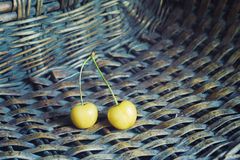 White cherry. Two white cherry in the wicker basket. Wicker basket texture at the background Royalty Free Stock Images