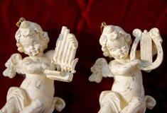 White Cherub Musicians. Cherubs playing flute and harp on red velvet royalty free stock photography