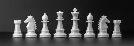 White chess figures isolated on the black background. Royalty Free Stock Images