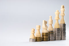 White chess figures standing on coins meaning power and career growth Stock Photos