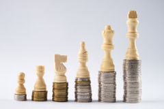 White chess figures standing on coins meaning power and career growth. Growing coins stacks on white background. White chess figures standing on coins meaning Royalty Free Stock Images