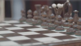 White Chess Figures. Unidentified hand setting up white chess figures on the board stock footage