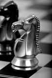 White chess horse on a board. White chess horse on a chess board with a black horse out of focus Royalty Free Stock Photography