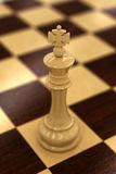 White chess king. On chess board - very shallow depth of field with focus on the top of the king Stock Images