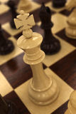 White chess king. On chess baord - very shallow depth of field with focus on the top of the king Stock Images