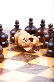 White Chess King checkmated by opposing team, white background, copy space. White Chess King checkmated and fallen down on wooden Chessboard, many black pawn stock photography