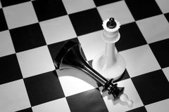 White chess king won the black one. Concept with chess pieces on a chessboard Royalty Free Stock Image