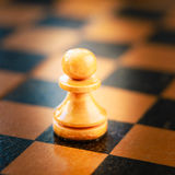 White chess pawn standing on chessboard Stock Image