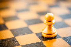 White chess pawn standing on chessboard Royalty Free Stock Photos