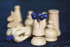 White chess pieces. Details of white wooden chess pieces, King is knocked over signifying end of game Stock Photography