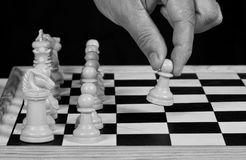 White chess pieces with hand playing Royalty Free Stock Image