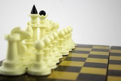 White chess pieces stand on a chessboard before the start of a game. White chess pieces stand on the chessboard before the start of a game stock image