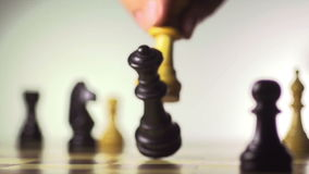 White chess player knocks down the black king with his piece stock footage