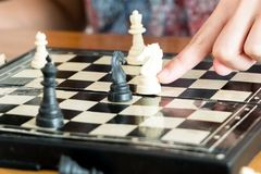 The white chess on women hand is fighting with black, think, discuss, committed, competition, winner, successful, dedicate concept Royalty Free Stock Image