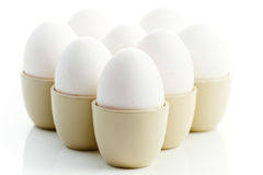 White chicken eggs in eggcups. On a white background Royalty Free Stock Photo