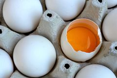 White chicken eggs are fresh, stacked in ecological cardboard packaging. One of the eggs is broken and the yolk is visible. Food. Background. Close-up royalty free stock photo
