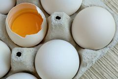 White chicken eggs are fresh, stacked in ecological cardboard packaging. One of the eggs is broken and the yolk is visible. Food. Background. Close-up royalty free stock photography