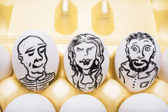 White chicken eggs with people`s faces painted on them Stock Photo