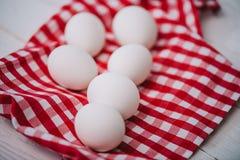 White chicken eggs on red. Plaid napkin royalty free stock photos