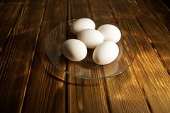 White chicken eggs in a transparent plate. On a rustic wooden table. Natural. Healthy nutrition, diet and fitness stock photo