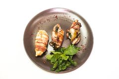 White chicken meat in bacon with greens royalty free stock photography