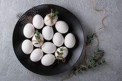 White chicken raw  eggs on a black plate. Top view and copy space. Easter  photo concept Royalty Free Stock Photos