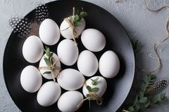 White chicken raw  eggs on a black plate. Top view and copy space. Easter  photo concept Stock Photos