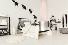 White child`s bedroom interior. White rug next to bed with knit blanket in child`s bedroom interior with black chair at desk with laptop Royalty Free Stock Image