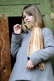 White child showing leaves. One girl presenting old leaves in front of painted entrance Stock Photography