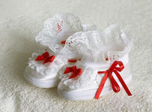White children's bootees, shoes on a light towel. White children's bootees, shoes with red bows and ribbons on a light terry towel. Textile footwear for kids Stock Image