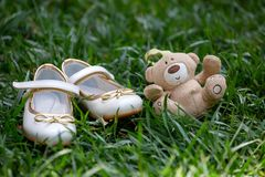 White childrens shoes and a beige bear lying on the grass. royalty free stock photography