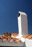 White Chimney. With red roof tiles and blue sky Royalty Free Stock Image